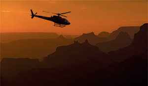 Helikopter som flyr over Grand Canyon ved solnedgang.